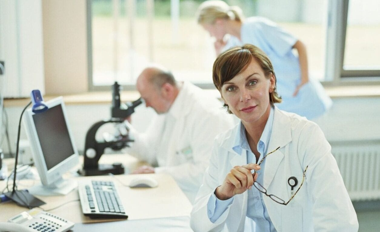 Eastern European Woman with a Scientific Research Team Using a Microscope