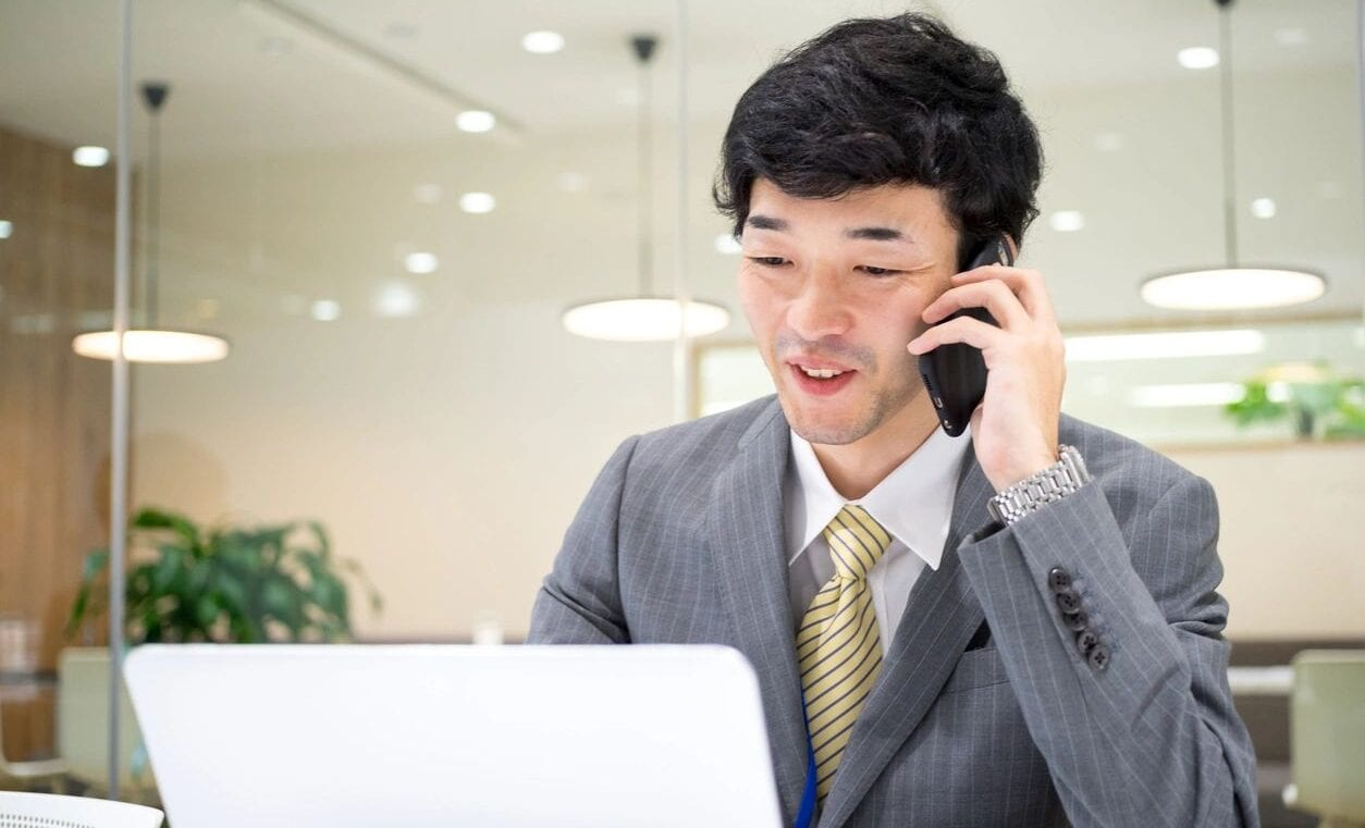 Korean Man in a Suit on a Cell Phone at an Office